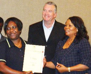 Josephine Nakatana receives her 15-year achievement award from Clara Bohitile, a member of the Windhoek Country Club Resort and Casino's board while Tony Boucher, general manager of the Country Club, looks on. (Photograph by Clemencia Jacobs)