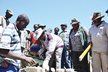 Right. Hon. Prime Minister Hon. Nahas Angula (front row: second from left) lays a corner stone to mark the official commencement of the construction of a permanent three classroom block and a store room at Otjomuru in the Epupa constituency, Kunene region on 10 December 2011, while Deputy Prime Minister Hon. Marco Hausiku and Hon. Angelika Muharukua, Deputy Minister of Gender Equality and Child Welfare look on.