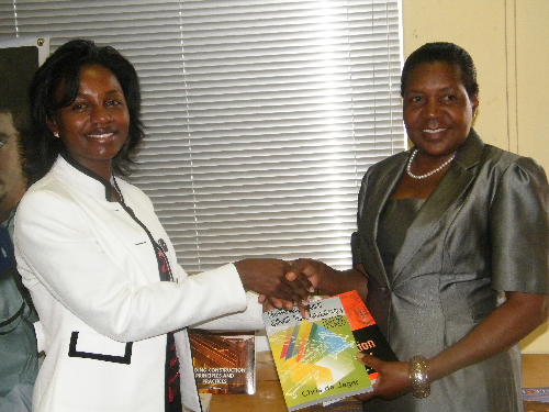 The Chief Executive Officer of the Namibia Training Authority, Maria Nangolo-Rukoro hands textbooks over to a representative of Zambezi VTC, Albertina Heita. (Photograph by Yvonne Amukwaya)