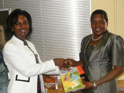 The Chief Executive Officer of the Namibia Training Authority, Maria Nangolo-Rukoro hands textbooks over to a representative of Zambezi VTC, Albertina Heita. (Photograph by Yvonne Amukwaya)