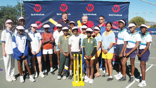 (Left to right): Graham MacMillan, CEO of Cricket Namibia, Riaan van Rooyen, head of Corporate Communication and Social Investment at Bank Windhoek and Romeo van Wyk, Ladies Cricket Coordinator of Cricket Namibia pictured with some of the girls who took part in the cricket festival.