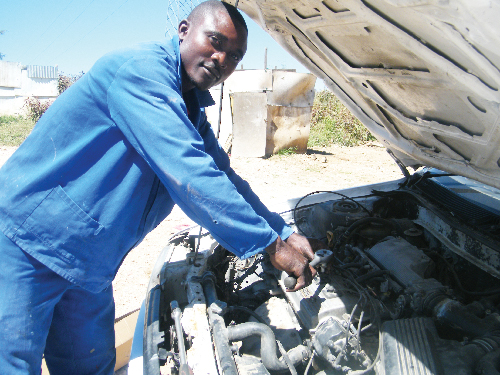 Kalimbo Timateus, a self employed mechanic, works from home in the informal settlements of Katutura. (Photograph by Yvonne Amukwaya)