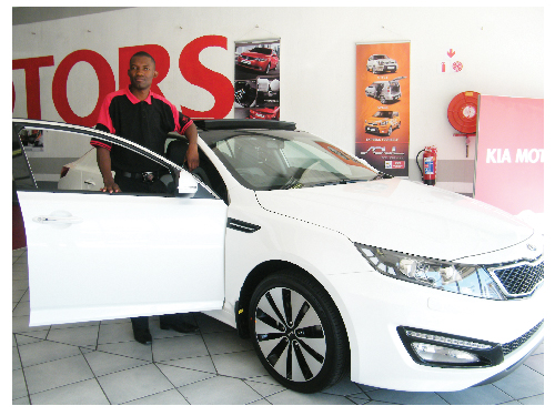 Cecil Karumendu with the newly launched 2012 Optima Sedan. (Photograph by Yvonne Amukwaya)