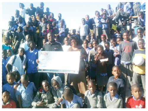 Ikolelela Ekandjo of Namibia Breweries handing the cheque for N$10,000 to Ms. Petrine Shiimi of the Oonte OVC Organization in Ondangwa, surrounded by the elated children who will benefit from this fundraising initiative. Oonte OVC in Ondangwa joined millions of children in southern Africa on the Day of the African Child to commemorate the uprising in Soweto, Johannesburg on 16 June 1976. They also used the Day to launch their own fundraising.