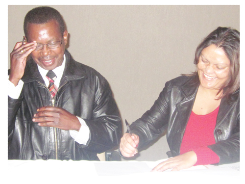 Chief Regional Officer, Dr. Bernard Mulongeni (left) and chief internal auditor, Ms. Daphne Feris (right) at the recent official signing of the first-ever performance agreement by the staff of the Khomas Regional Council in the capital. (Photograph by David Adetona)
