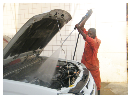 Hafeni Ailonga of the WIKA Car Wash using a high-pressure pipe to wash away dust from the engine before cleaning it. A good engine cleaning can also be done at home. (Photograph by Hilma Hashange)