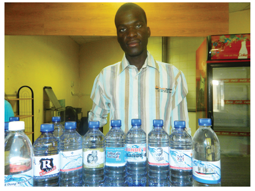 Jacob Hamutenya with some samples of personalised labelled mineral water by Omulaule Investments (Photograph By Hilma Hashange)