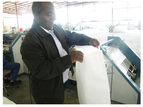 Francis Lunga holding a finished bag (Photograph by Hilma Hashange)
