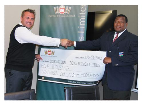 Managing Director of the Breweries, Wessie van der Westhuizen handing the sponsorship cheque to Minister Mutorwa on Monday.