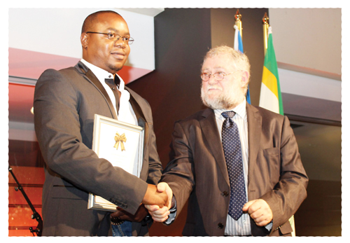 Docky Olavi receiving the award from Deputy Minister of Finance, Calle Schlettwein