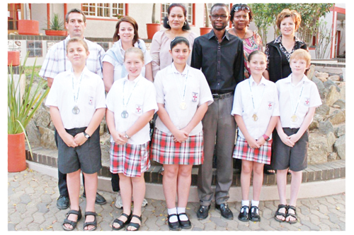 Principal, Mr D Leibbrandt, with teachers Ms C Mans, Mrs F Khaiseb, Mr C Mutambo, Ms N Kangumine, Mrs B Maritz and the brainy bunch. Liam Brinkmann won a silver medal, Helen Forster, also silver, Monique Pedreiro, a gold, Kyla Grobler, also gold, and National category winner in the Primary Section, Bradley Sisson who also walked away with a gold medal.