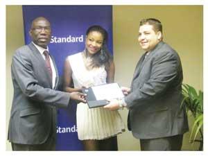 Head of Marketing at Standard Bank Namibia Thaddius Maswahu, Miss Namibia Tsakana Nkandih, and Standard Bank Ausspanplatz Branch Manager, Dewald Swart at the opening of Miss Namibia 2012's Basic Blue account. (Photograph by Melba Chipepo)