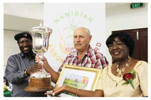 Hon Petrus Ilonga (left) congratulates Mr Hansie Opperman, Champion Large Scale Producer of the Year.Hon Sophia Shaningwa, Governor of the Omusati Region is on the right.