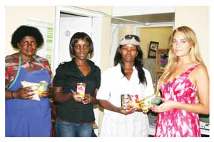 Marta Kamutjemo, Elizabeth Nakayima and Charmaine Thomas from Friendly Haven Shelter receiving donations from Sister Namibia intern, Sanne Klasen.  Photo by Sheena Magenya