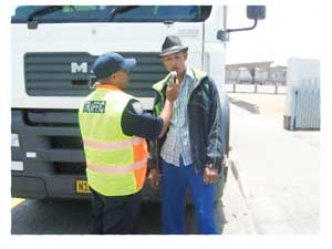A traffic officer administering a breathalyser test to a truck driver.