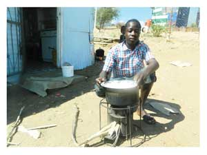 Diob Kauapirura heating water on an Ezystove (Photograph by Hilma Hashange)