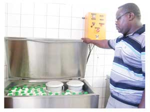 Jafta Ngavetene at the pasteurisation machine. (Photograph by Hilma Hashange)
