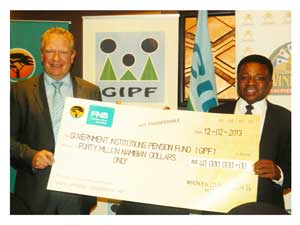 The Chairman of the Board of Directors of the Windhoek Country Club Resort and Casino, Sven Thieme hand a cheque for the remaining N$40 million of a loan it took from the GIPF in 1994, to David Nujoma, CEO of the GIPF. (Photograph by Lorato Khobetsi)