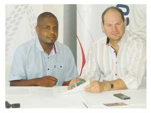 Nelson Herunga, Vice Chairperson of the Namibian Squash Association signs a sponsorship agreement to the tune of N$1.5 Million with Quinton van Rooyen, Managing Director of Trustco Group Holding. (Photograph by Hilma Hashange)