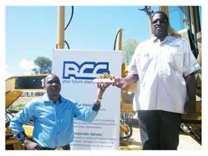 Chief Executive Officer for the Roads Construction Company (RCC) Engehard Haihambo receives a miniature grader from Barloworld Equipment Namibia's Operations Manager Elias Nandiwa. (Photograph by Melba Chipepo)