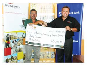 Christie Benade, Executive Director of Lake Oanob Resort receiving the sponsorship from Wessie van der Westhuizen, Managing Director of Namibia Breweries Limited. (Photograph by Hilma Hashange)
