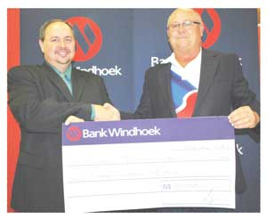 Paul Schrader, Branch Manager of the Bank Windhoek Swakopmund Branch hands over the sponsorship to David Gibbons, Captain of the Rossmund Bowls Club.