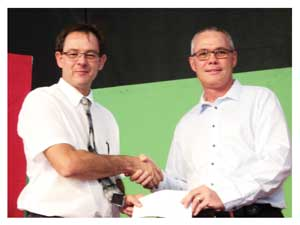 Paul du Plessis (left), the principal of Dagbreek School receiving the cheque from Pottie de Bruyn, Country Sales and Marketing Manager of Coca Cola. (Photograph by Hilma Hashange).