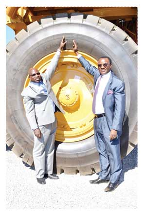 Minister of Mines and Energy, Hon. Isak Katali, left, is overwhelmed by the size of a mine dump truck as eloquently explained by the mining company's chairman, Dr Leake Hangala.
