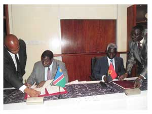 Assisted by Engene Kanguoatjivi from the Ministry of Agriculture, Water and Forestry's International relations department (Left) and Mendes Fransisco, 1st Secertary at the Angolan Embassy (Right),  Agriculture Minister, John Mutorwa and Minister of Agriculture from Angola, Alfonso Pedro Cango signs the MoU on the control, prevention and eradication of transboundary animal diseases with specific references to Foot and Mouth disease and lung sickness.(Photograph by Lorato Khobetsi)