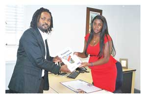 Budding investor, Nathan Kashweka, receiving his prospectus from Maggy Shixungileni of Bank Windhoek Capricorn Branch.