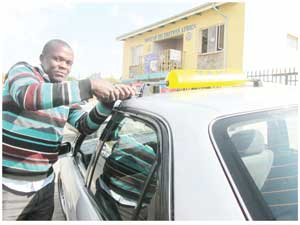 Kondjeni Petrus Manyami seen here fitting a taxi sign to the roof of a customer's car. He charges N$30 for his services.