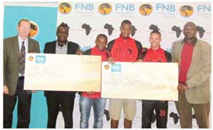FNB CEO Ian Leyenaar (left), Ranga Haikali (far right) Chairman of Black Africa with some of the Black Africa players at the handover ceremony of the bonus cheque ( photograph contributed)