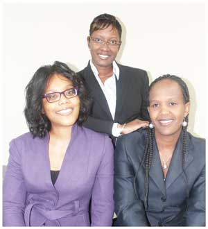 Women in Leadership at Standard Bank Namibia: Saara Shivute (standing) Manager Operations Shared Services; Head of Legal Services, Magano Erkana and Manager of Operations Control, Uanjengua Katjiuanjo.
