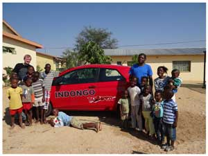 Omaruru Children's Haven manager, Andreas Moeckel (left) and principal, Lazarus Musambani (right) with the children and the small red Toyota Yaris donated by Standard Bank.
