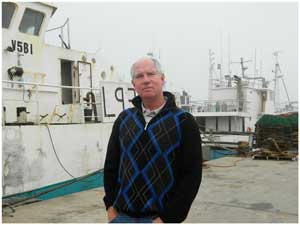 Freddie Fish Processors' Managing Director, Wayne Hart in a pensive mood next to one of the trawlers of which they regularly process the cargo.