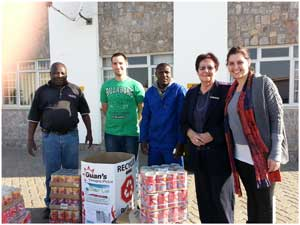 Sylvan Shetuyenga (left) from Ocean Liner Service, assisted by Tyron Roets presented the gift of canned for to Duif Greeff, Matron of Huis Palms Old Age Home. On the right stands Soenet van Biljon, also from Ocean Liner.