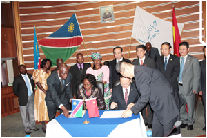 Her Worship, Cllr. Agnes M. Kafula, Mayor of the City of Windhoek and Xu Songnan, Member of the Standing Committee of CPC Chongqing Municipal Committee, signing the Memorandum of Understanding while Hon. Laura McLeod Katjirua, Governor of the Khomas Region, City Councillors and other members of the visiting delegation witness the event.