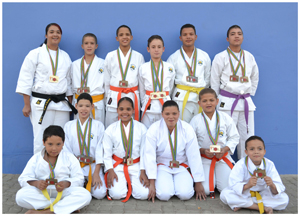 Proud medal winners at the recent International Development Karate Championship in South Africa are, front row seated from the left, Valentino Louw (bronze in kata), Rach-Zaune Klaaste (silver in kata, bronze in kumite), Caitlin Louw (gold in kata, bronze in kumite), Shaniqua Hagemann (bronze in kumite), Marliyano Tripodi (gold in kumite,bronze in kata) and Stanfo Kruger (bronze in kata); back row standing, Sensei Morchen Kruger (gold in kata), Wilhermo Johr (bronze in kumite and bronze in kata), Stéfan Vries (bronze in kata), Ernst Hagen (gold in kumite and gold in kata), Ryan Bock (silver in kata, bronze in kumite), Ryan Kruger (bronze in kumite and bronze in kata). (Photograph by Klaus Johr)