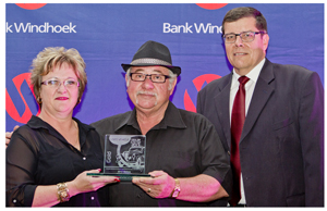 Flamboyant car dealer, Dirk Levin (with hat) of M&Z Motors accepting the gold award in the Best Used Car Dealership category of the 2013 Bank Windhoek Selekt Sales awards. On the left is Sandra Blaauw, Manager of the bank's Vehicle and Asset Finance branch. Chris Matthee, Bank Windhoek's Executive Officer for Retail Banking Services (right), checks on Dirk to make sure he leaves the stage with the right trophy.