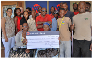 Members of the Namibia Federation of the Visually Impaired (NFVI) receiving the cheque from Elzita Beukes (standing far left), Communication Practitioner: Stakeholder Engagement at Bank Windhoek.