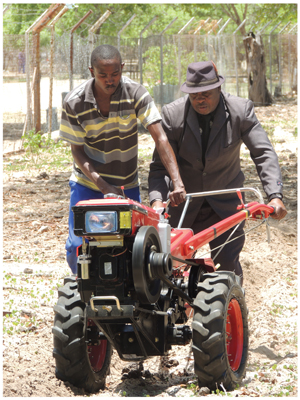 Sam Matheus (left), a level 1 student from NIMT Tsumeb on a six-month work attachment at Komeho Namibia's Okongo Appropriate Rural Technology Centre, demonstrates the power and ease of operation of a walking tractor to Okongo constituency counciilor, Paulus Mwahanyekange. The walking tractor is one of the large range of agricultural equipment offered by Komeho and financed by Kongalend through its new Lima Power loan product.
