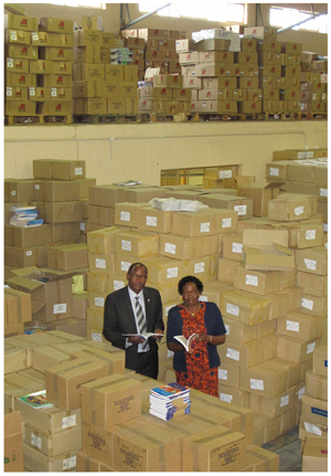 Dwarfed by almost a million textbooks, the CEO of the Millenium Challenge Account (MCA) Namibia, Ms Penny Akwenye (right) is joined by the Minister of Education, Hon Dr David Namwandi earlier this week when the MCA presented the ministry with textbooks for this year.
