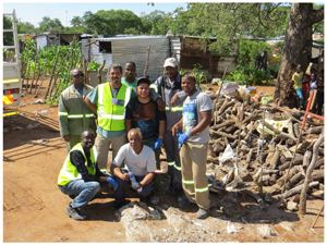 Standing from the left are B2Gold employees and volunteers, Ivan, August, Hendrik, Morné, Wilfried, and Rocky. In the front, Kaanduka Nghipandulwa, B2Gold Stakeholder Liaison Officer, takes time to appreciate the stack of wood supplied to Eugene Reineke (right).