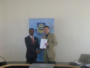 Prof. Tjama Tjivikua, Rector of the Polytechnic of Namibia and Prof. Oliver Gunther, President of the University of Potsdam holding the memorandum of understanding they just signed. (Photograph by Mandisa Rasmeni)