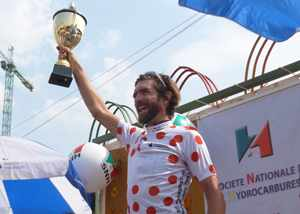 An ecstatic Dan Craven celebrating with the overall winners trophy and King of the Mountain jersey at the Tour du Cameroun.