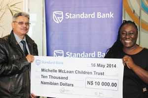 Project Manager of the Michelle McLean's Children's Trust, Fritz Zender (left) receiving Standard Bank's sponsorship from its PR & Communications Manager Surihe Gaomas-Guchu.
