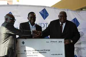 Minister of Mines Isak Katali appears to be all smiles as Chief Executive of the Namibia Diamond Trading Company, Shihaleni Ndjaba, hands over a cheque totalling N$50 million while Chairperson of the NDTC Festus Mbandeka witnesses.