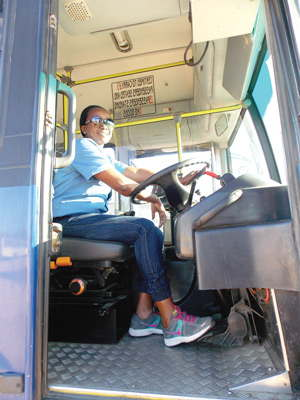 Mrs Annelly Ngwedha the only female bus driver at the City of Windhoek, demonstrating how comfortable she is behind the steering wheel of a bus. (Photograph by Mandisa Rasmeni)