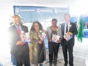 (L-R) Junius Mungunda, Chief Executive of Standard Bank, Katrina Hanse-Himarwa, Hardap Regional Governor, Dr Ndapewa Hamunime, CSI Board Chairperson of Standard Bank and Herbert Maier Board Chairman of Standard Bank  holding the Standard Bank Corporate Social Investment Report of 2013. (Photograph by Mandisa Rasmeni)