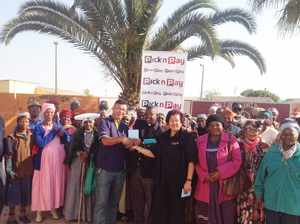 The Reverend Simon Kheib (centre with clerical collar) of the Luthen Old Age project in Swakopmund, receiving a voucher from Henry Feris, Pick n Pay Namibia's Managing Director (centre left). Next to the Reverend is Pick n Pay's manager of the Swakopmund branch, Cecilia Samaria. Witnessing the occasion are the residents of the old age home.